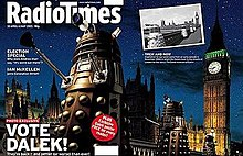 "A gatefold magazine cover, depicting a nighttime scene with four gold Daleks in the foreground, the railing of a bridge in the midground, and the Perpendicular Gothic towers of the Houses of Parliament and Big Ben in the background. The left half of the image contains the text ""Radio Times"" in the top, and ""VOTE DALEK!"" in the lower left. A small black-and-white photograph is superimposed on the upper left of the right side of the image; that photograph, taken from a slightly different angle, shows four Daleks crossing the same bridge, with the same building in the background."