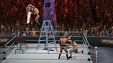 A shirtless masked wrestler attempts to slam a wrestler wearing blue and white striped shorts through two stacked tables, another wrestler wearing jean shorts and sneakers punches a fourth wrestler who is holding his head. All four are in a wrestling ring with a ladder at the center and a briefcase hanging above the ladder, in front of a crowd.