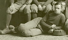 Posed sepia-toned photograph (apparently cropped from a team photograph) of Hughitt wearing a football uniform reclining on the floor