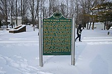 State of Michigan Historical marker with gold text on a green background, standing in a field of snow