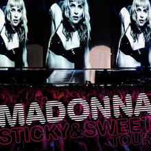 "The upper part shows three similar image of a blond woman, wearing a black bra. Her right hand is held up. The lower part shows a crowd looking at her. On top of them, the words ""MADONNA"" and ""STICKY & SWEET TOUR"" is written."