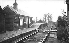 "A small wooden hut labelled ""Westcott"". In front of the hut is a deserted low wooden railway platform with a short section at a much greater height; the only objects on the platform are three large lamps. A single railway track leads past the platform; the line branches immediately past the end of the platform. A cat is asleep on the railway track."