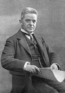Carl Nielsen, seated, facing right, smartly dressed in a suit and waistcoat