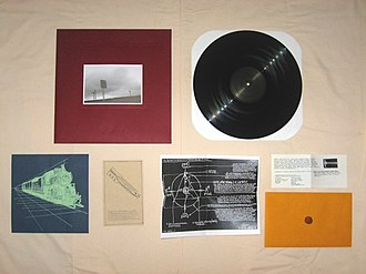 F♯ A♯ ∞ - The record and its many inserts laid out, including the crushed penny. The hand drawn picture by Efrim Menuck is visible between the handbill and envelope.