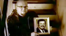 Sitting on stairs, Bart Millard holds up a picture frame of his father Arthur