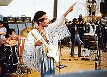 Una imagen en color de tres hombres de pie en el escenario actuando música