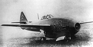 Black-and-white three-quarter view of jet aircraft on grass. The engine inlet is in the nose.