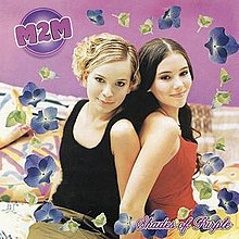 Two teenage girls, one blonde and one brunette, sitting on a bed in front of a purple wall. The girls are surrounded by watermarks of violets. 'M2M' appears in the upper left corner and 'Shades of Purple' appears in the bottom right.