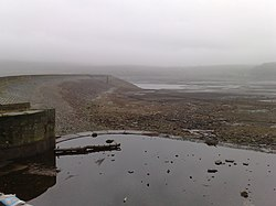 Image of an almost dry reservoir in heavy mist