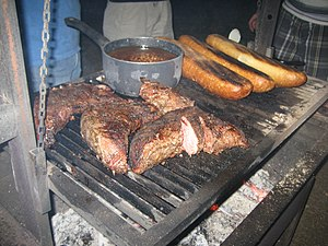 Santa Maria-style barbecue - Tri-tip on the grill, with a saucepan of beans and loaves of bread