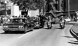 Ike Altgens - Altgens' sixth photograph of the motorcade, and his first during the assassination of John F. Kennedy. The Elm Street doorway to the Texas School Book Depository is seen behind the limousine. This area soon became the focus of private research and official investigations. See § The man resembling Lee Harvey Oswald.
