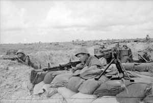 Soldiers wearing helmets lie behind their weapons on a wall of sandbags, while in the background other soldiers are loading an artillery piece which is laid on a low trajectory.