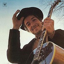 Dylan looking down at the camera while holding a guitar, smiling, and doffing his cap