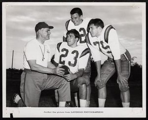 Clarence Stasavich - Stasavich kneeling beside three senior football players at East Carolina