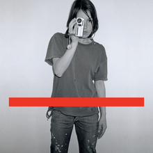 A black-and-white photo of a woman taking a photo with a red line.