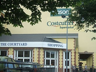 """Courtyard Shopping Centre - """"Eat for Less, Dress for Less - Go on have a Courtyard day""""   The rear entrance of the Courtyard as viewed from the Government Offices on Oliver Plunkett Street."""