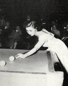 Black-and-white photo of Japanese woman in fancy dress, approximately 30 years old, stretched out over corner of carom billiards table with her cue stick in hand. Her eyes are intently focused on the shot in front of here, two billiards balls about a foot apart, with her cue tip about two inches behind the closest ball in position for the hit; the table scene is in spotlight and in the much darker background can be just made out spectators in chairs, all appearing to be men.