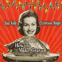 A sepia coloured image of a woman presenting a platter containing a large roast bird (possibly a turkey). Her smiling face is visible beyond the bird, her fingers appear below the platter. The background is red. A strand of coloured Christmas lights stretches across the top of the image. The artist's name is located to the left of the woman's head and the words, Christmas Single, are to her right. The title of the single is written over the image of the roast bird.