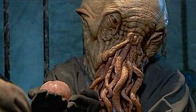 A captive alien with tentacles on its face holds an external hindbrain in its hands.