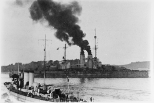 A large battleship steams through a harbor. Large clouds of smoke can be seen coming from the ship's funnels while a smaller vessel is sailing in the foreground. Hills and the coastline can be seen in the background.