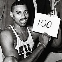 Wilt Chamberlain, an African American man, is shown sitting down in his Philadelphia Warriors jersey while holding up a piece of paper with the number 100 written on it. The photograph was taken directly after the game and is in black and white.
