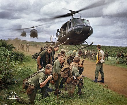 An iconic image of Australian soldiers from 7 RAR waiting to be picked up by UH-1 Iroquois helicopters following a routine cordon and search operation. 7 RAR Vietnam (AWM EKN-67-0130-VN).jpg