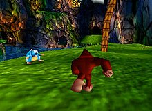 A brown gorilla runs across a green expanse of blurry green. A palm tree grows in the back right corner and a dark jungle background shows in the distance.