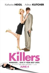 Heigl left holding a gun between her forefingers at arms length, Kutcher with a gun held close to his chest.