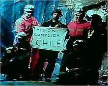 "Slightly grainy color video capture image of the six rescuers displaying the famous ""Mision Cumplida Chile"" sign deep within San José Mine near Copiapo, Chile[126]"