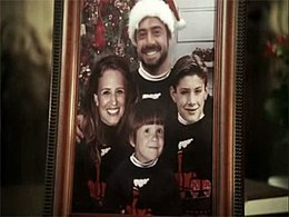 A framed Christmas family portrait. The father, mother, and two sons are wearing identical sweaters.