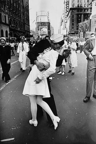 "V-J Day in Times Square - V-J Day in Times Square, a photograph by Alfred Eisenstaedt, was published in Life in 1945 with the caption, ""In New York's Times Square a white-clad girl clutches her purse and skirt as an uninhibited sailor plants his lips squarely on hers"""
