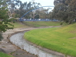 Dandenong creek and pedestrian bridge at Dandenong Park.png