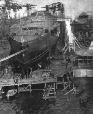 The hull of a large ships in a shipyard, surrounded by scaffolding and cranes