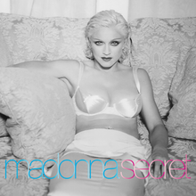 Madonna in a white dress sitting on a sofa and smiling