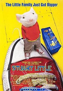 A smiling white mouse standing atop a big sneaker. A blue suitcase sits beside it.