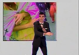 "A still from the ""Once in a Lifetime"" music video. Singer David Byrne, dressed in a suit, bowtie and glasses, mimics the hand movements of a woman performing a ritual dance."