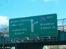 A green sign on an overpass reading Grand Central Parkway east LaGuardia Airport left straight on left three lanes I-278 west Brooklyn Staten Island right lane exit 1/2 mile