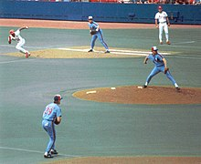 A St. Louis runner breaks from first base as the Expos pitcher throws to the plate.