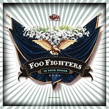 "Against a background with white and green stripes lies a crest with banners, flowers and an eagle. Below the eagle is the title ""Foo Fighters - In Your Honor"" and four stars. Above the crest is a buffalo."