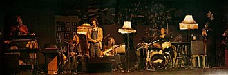 Henry Cow - Henry Cow performing in Fresnes, France, 16 November 1975.   Left to right: Tim Hodgkinson, Lindsay Cooper, Dagmar Krause, John Greaves, Chris Cutler and Fred Frith.   (The fringed sitting-room standard lamps accompanied them throughout the 1975 tour).
