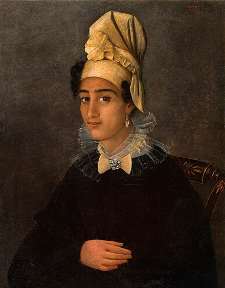 A young Creole woman in a tignon of her own creation. Note that the rosette in the tignon is repeated as either a brooch or in the linen at her neck. Painting from the Historic New Orleans Collection. Portrait of Betsy.jpg