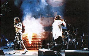 "Killing in the Name - Rage Against the Machine burning the American flag onstage while playing ""Killing in the Name"" during Woodstock 1999."