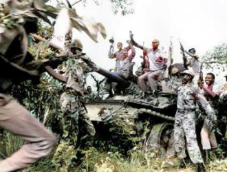 Second Sudanese Civil War - Guerrilla forces of the Sudan People's Liberation Army celebrate over a disabled tank.