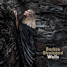 Barbra Streisand wears a black shall, gazing upward, surrounded by a large stone wall