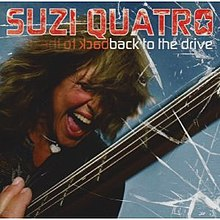 The front cover of Suzi Quatro's album Back to the Drive. Quatro is in close-up, with only her head and one of her shoulders visible. She is screaming while playing a bass guitar, with graphics that make the cover appear to be a window that she has shattered. One of her eyes is closed; the other is covered by her hair. She is wearing a black leather jacket and a silver necklace with a silver heart on it. Behind her is a light blue background.