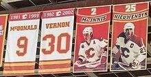 """Quatro faixas retangulares estão penduradas nas vigas de uma arena de hóquei.  Os dois na extrema esquerda são predominantemente brancos com detalhes em vermelho e dourado.  O esquerdo diz """"1981-1989 McDONALD 9"""" e o direito """"1982-2002 VERNON 30"""".  Do lado direito deles, mais dois banners são mostrados.  Ambos são principalmente vermelhos, cada um mostrando (de cima para baixo) um número, em seguida, uma faixa vermelha com detalhes dourados mostrando um nome e, por último, uma pessoa em uniforme completo de hóquei, que é mostrada vestindo uma camisa branca com detalhes em vermelho e um capacete branco .  O esquerdo diz """"2 MacINNIS"""", enquanto o direito diz """"25 NIEUWENDYK""""."""