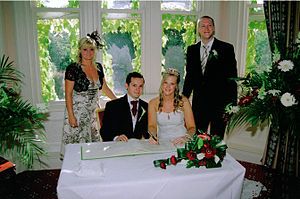 Civil ceremony - Signing of the marriage register with witnesses present, at Sprowston Manor, UK.