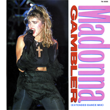 "A blond woman wearing a black pant and top, with a crucifix around her neck. Her blond hair is unkempt and a part of it is tied at the top of her head. She also wears black gloves on her hands. Beside the image, the words ""Madonna"" and ""GAMBLER"" are written in slant, with the first being in pink color, the latter in red."
