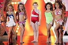 A film screenshot showing five girls standing on stage at the pageant at the end of the film. From left to right, the first girl (wearing a one-piece swimsuit) has her left leg placed in front of her right, the second girl (wearing a two-piece swimsuit) has her legs shifted in the opposite direction, at center the main character (wearing a one-piece swimsuit) is standing straight, the fourth girl (wearing a one-piece swimsuit) has her left leg placed in front of her right, and the last girl (wearing a two-piece swimsuit) also has her left foot forward. All of the girls are smiling towards different angles, the background of the stage is decorated and it is reflected on the shiny surface of the stage.