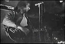 Upper body shot of a man playing a guitar with letters G-e-o visible. His head is turned partly to his left. There is a microphone stand in front of him. Other musical and studio equipment is around him. Another musician is obscured at bottom right.